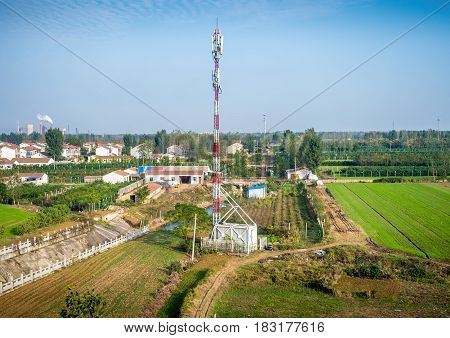 Tianjin, China - Nov 1, 2016: Image captured on High Speed Rail (HSR) from Tianjin to Shanghai, passing countryside with a quiet farming township. Features a telecommunications tower. Average speed: 300 km/hr.