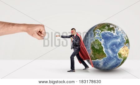 A small businessman in a red cape and a mask punching a giant fist with a small earth sphere behind him. Protecting business. Fight for clients. Global operations.