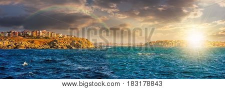 composite summer seascape. panoramic view of old resort town under the rainbow on a rocky cliff above the seashore. blue and calm water in the sea at sunset;