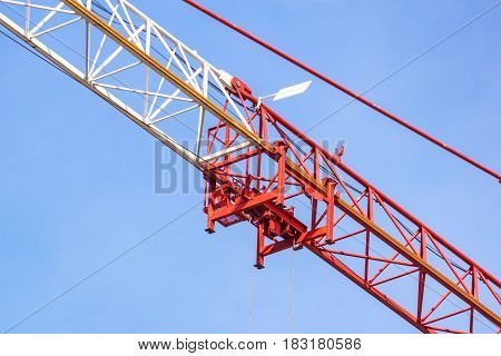 Red construction tower crane with grey jib and hook isolated on blue sky with white clouds background, detail