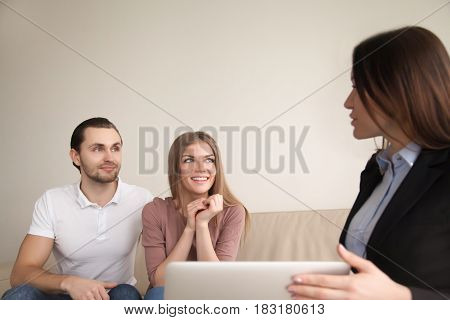 Smiling couple discussing future vacation with travel agent, man and woman planning real estate purchase consulting with broker, female agent explaining attractive mortgage offer to young happy family