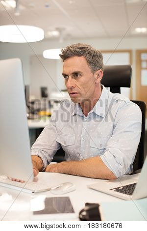 Serious businessman working on computer at desk in office