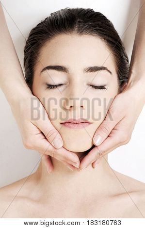 Beautiful young girl in spa. Facial massage, isolated on white background.Spa, beauty, health and scincare treatment concept.