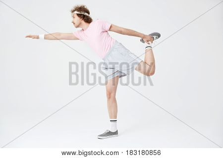 Side shot of man doing horizontal position on one leg with right hand up