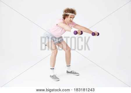 Young skinny man does squats holding light dumbbells, building leg muscles. Looking motivated and concentrated