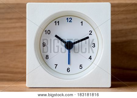 Modern white clock with vintage wooden background