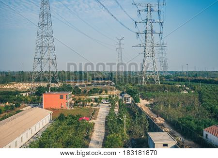 Tianjin, China - Nov 1, 2016: Image captured on High Speed Rail (HSR) from Tianjin to Shanghai, passing countryside with buildings under power transmission towers. Average speed: 300 km/hr.