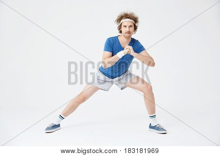 Sporty retro guy in old fashioned sport suit doing stretching exercises. Isolated on white background