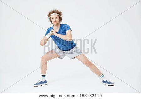 Deep side lunge position. Retro man in old style clothes warming up left leg muscles