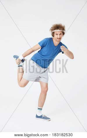 Guy stretching leg holding foot with right hand pointing at camera with pointer finger