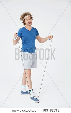 Man exercising with jumping rope isolated on white background winking at camera with right eye