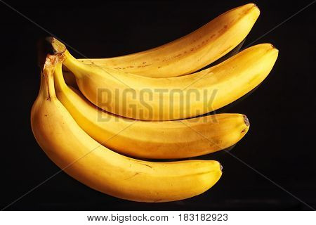 A bunch of ripe bananas isolated on a black background