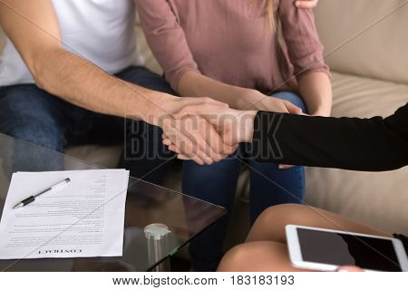 Close-up of man shaking hands with female banker after signing loan contract, health care insurance agreement, couple making deal on a matter of employment, advisory and consulting, tourist services