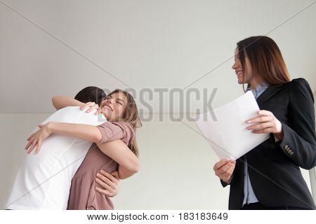 Excited couple hugging standing next to female real estate agent, first look at newly-built apartment, young family reaching goals and enjoying dream home purchase, view from below
