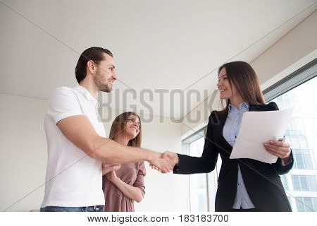 Real estate agent showing apartment to young man and woman, cheerful smiling couple shaking hands with friendly realtor holding papers, client and businesswoman handshaking, business greeting
