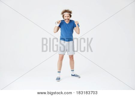 Man biting skipping rope holding it in hands. Looking agressive and motivated before training