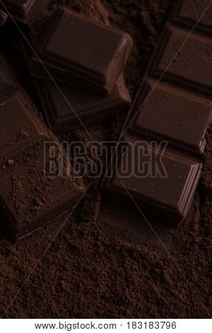 Close-up of a dark chocolate bar blocks covered in chocolate powder on a table