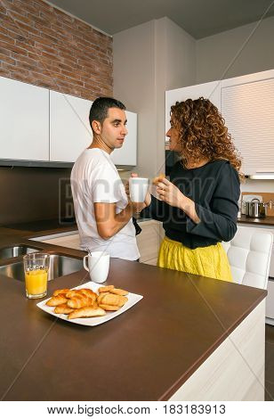 Young man having fast breakfast in home with woman ready to go to the office