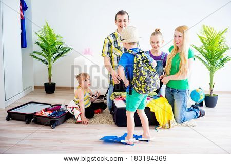 Happy family packing suitcases for a trip holiday travel vacation