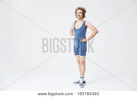 Retro man in old fashioned blue sport suit looking straight, posing with arms akimbo