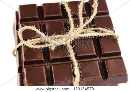 Three pieces of bitter dark chocolate bar bound by twine isolated on white background close-up view.