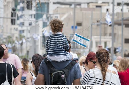 TEL AVIV, ISRAEL. May 2014. Father and a child walking with the crowd in the Tel Aviv promenade during the Independence Day of Israel.