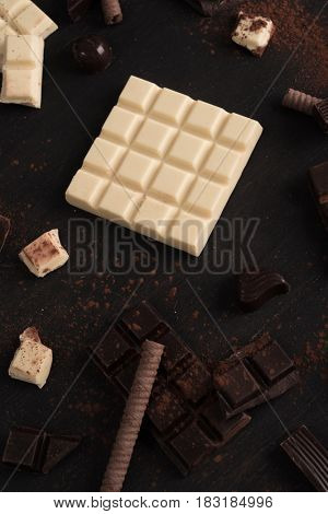 Top view of chocolate bar pieces and candies over wooden surface