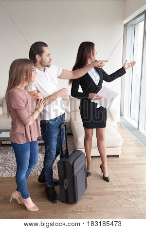 Young travellers with travel baggage suitcase meeting with estate agent, apartment viewing, looking through the window asking about sights of the city, flats for daily rent, vacation home rentals