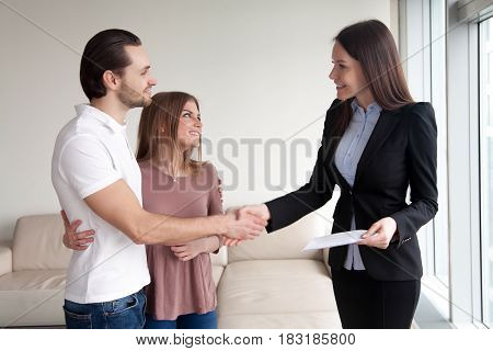 Portrait of couple making successful real estate deal with broker, visiting notary office, clients and female lawyer shaking hands, handshaking investment advisor, satisfied customers and manager