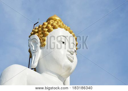 white Buddha image in Wat Phrathat Doi Kham ancient temple in Thailand