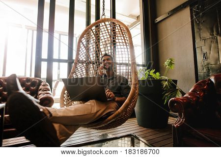 Young man sitting on a wicker hanging chair in office lounge with laptop and talking on mobile phone. Business man relaxing in office lounge during break.
