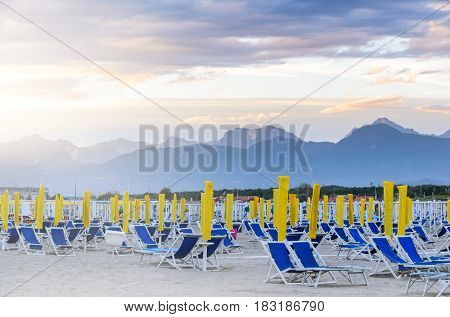Ready to open beach. Morning seats and umbrellas at seaside.