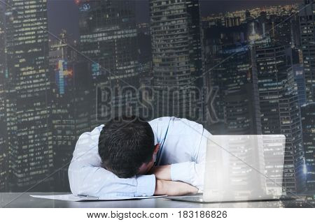 Tired business man is sleeping at his table with laptop