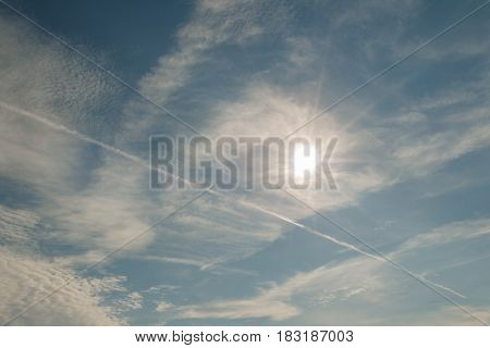 Blue sky with clouds, airplane trails and the Sun. Nature composition in Crimea, Ukraine 2011.
