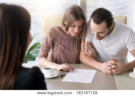 Smiling family couple reading contractual terms before signing contract, examining documents to make decision about mortgage, considering investment in property, calculating total loan liabilities