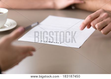 Close up view of contract, male hand pointing at some contractual terms, female offering to put a signature, basics of writing contract, negotiations for a deal, discussing document before signing