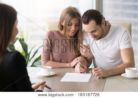Smiling couple agreed to sign prenuptial contract, handsome man putting signature on document while sitting together with his wife, taking bank loan, health insurance, signing financial papers