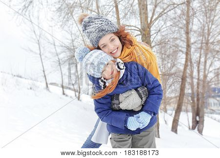 Mother with daughter playing in winter park