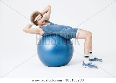 Guy in blue jumpsuit working on belly muscles looking straight. Stomach training concept. Retro style