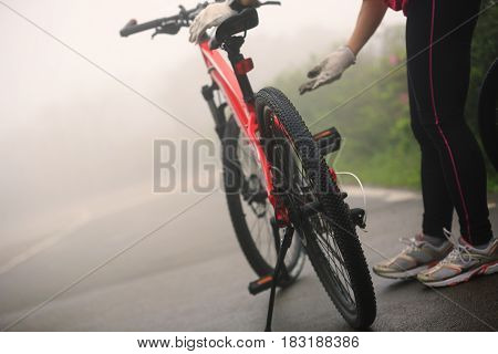 cyclist fix the bike chain on foggy road