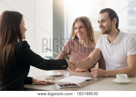 Meeting with agent in office, buying renting apartment or house, buyers of real estate ready to conclude a deal, family couple shaking hands with realtor after signing documents for realty purchase poster