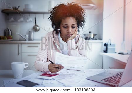 Young single upset african american housewife sitting at kitchen table with papers laptop and calculator trying to make both ends meet having no money to pay debts. Financial problems concept