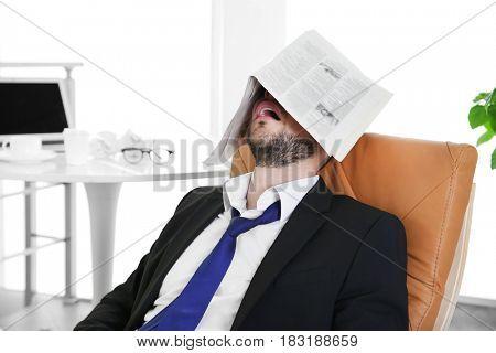 Business man sleeping under newspaper at workplace