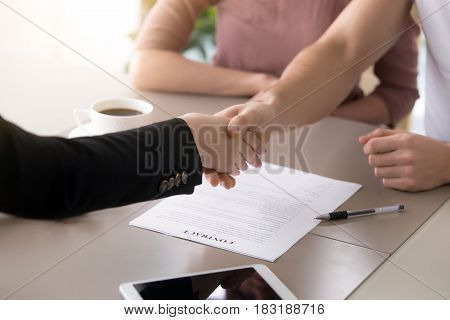 Male customer and female insurance broker shaking hands, couple and real estate agent handshaking after signing document, close up of making deal with satisfied clients, contract with a firm