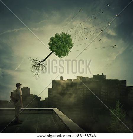 Surreal view as a boy stand on the rooftop looking at a flock of birds carrying a tree pulled from roots flying over the polluted foggy city. Town conservation and greening concept.