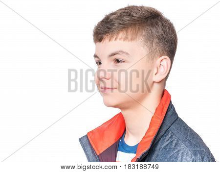 Close up emotional portrait of caucasian smiling teen boy. Head shot of handsome guy. Funny cute teenager, isolated on white background. Child looking away.