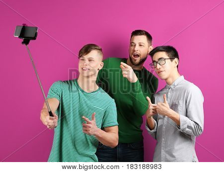 Young friends taking selfie on color background