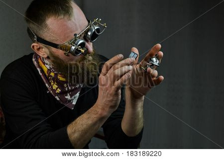 Steampunk man wearing glasses and keeping robot