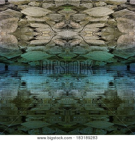 Rock structure with Aztec stone mosaic reflecting in water. Water surface with relief embossed rock