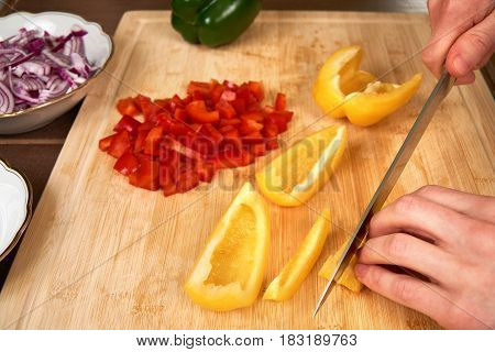 Cook chops ingredients for a meal on a cutting board in the kitchen.